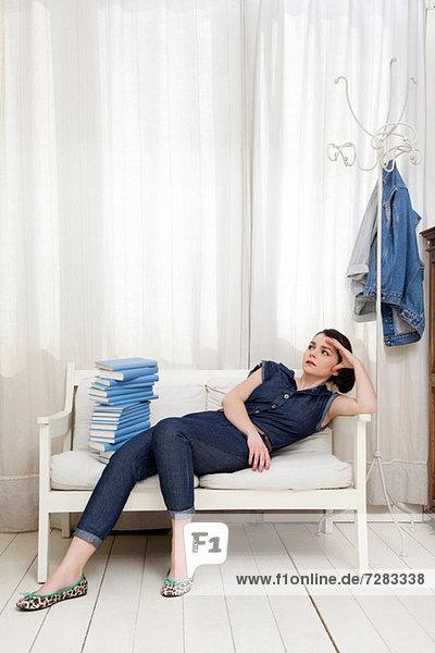 Frau auf dem Sitz liegend mit Bücherstapel