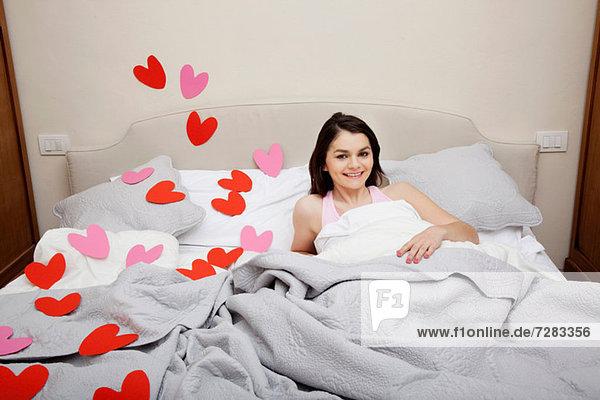 Frau im Bett mit Herzformen auf Bettwäsche