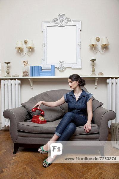 Frau auf dem Sofa nimmt Telefonhörer ab