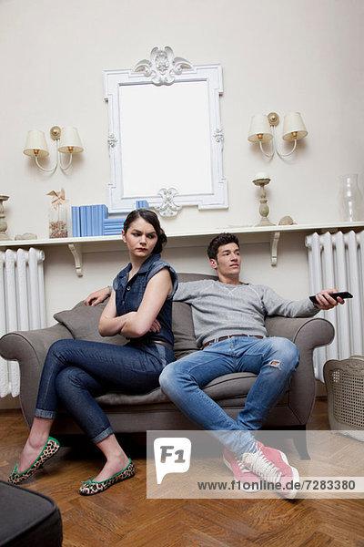 Couple on sofa  woman ignoring man