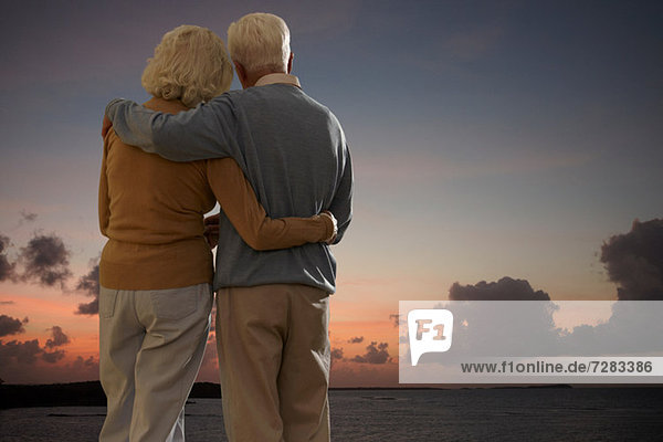 Seniorenpaar mit Blick aufs Meer bei Sonnenuntergang