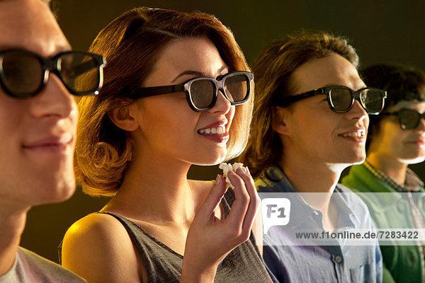 Reihe von Leuten  die sich einen 3D-Film ansehen  Frau mit Popcorn
