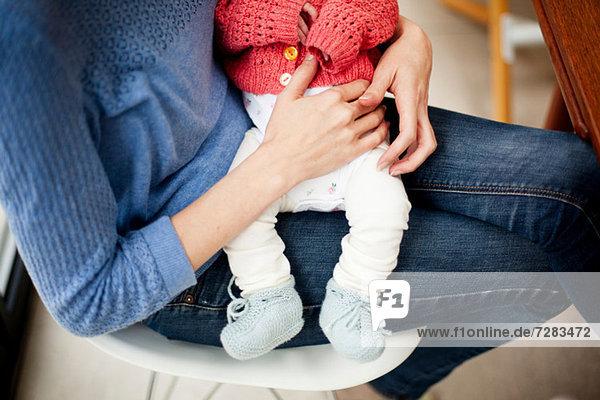 Mutter hält neugeborene Tochter  zugeschnittenes Bild