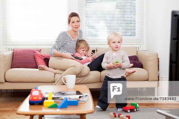 Mutter mit zwei Kindern beim Fernsehen