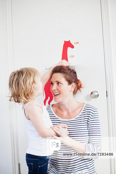 Tochter messende Mutter auf dem Höhendiagramm