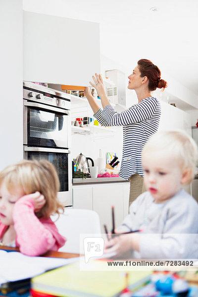 Mutter öffnet den Küchenschrank
