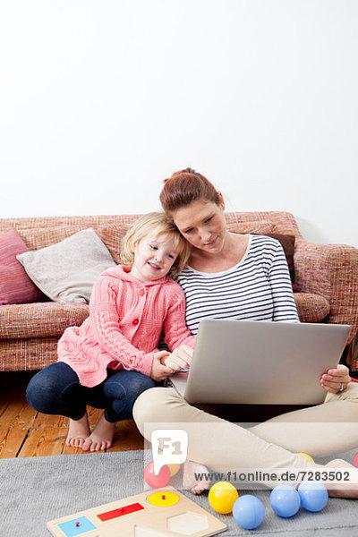 Mutter mit Laptop und Tochter