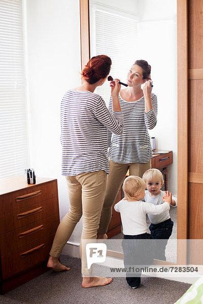 Frau beim Schminken mit Sohn am Spiegel