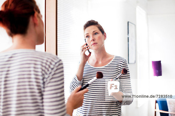 Woman on cell phone applying make up