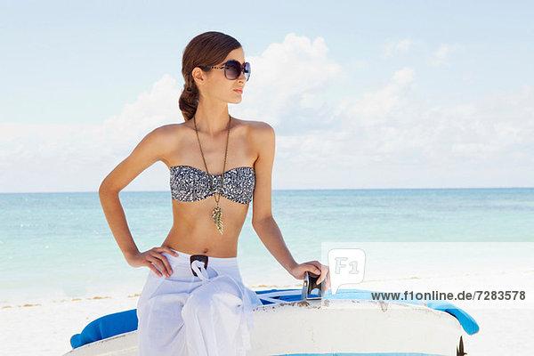 Junge Frau auf dem Boot am Strand sitzend