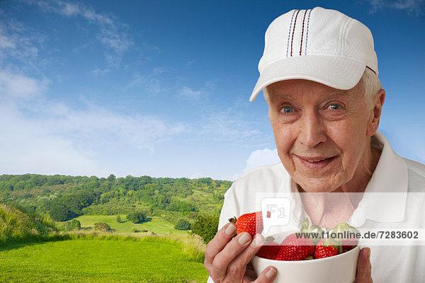 Älterer Mann in Tenniskleidung mit Erdbeeren gegen die ländliche Szene