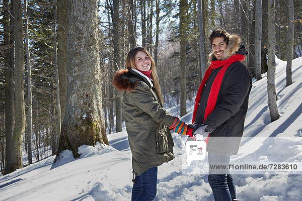 Paar hält Hände im Schnee