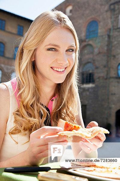Junge Frau im Restaurant im Freien mit Pizzastückchen