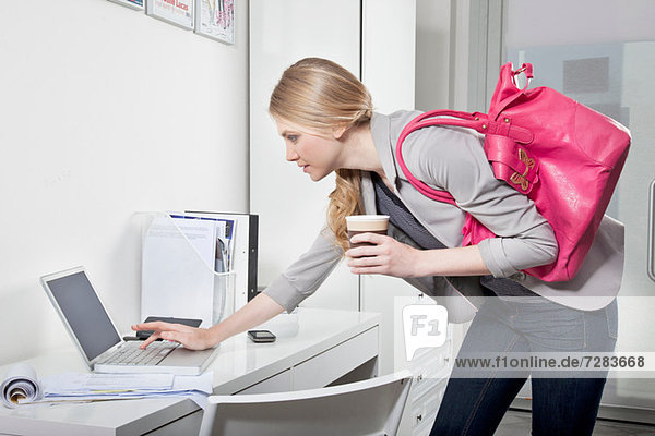 Junge Frau überprüft E-Mails im Büro