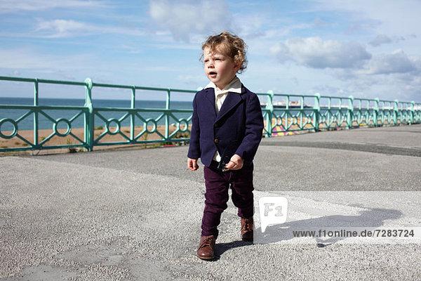 Kleiner Junge  der in modischer Kleidung spazieren geht.