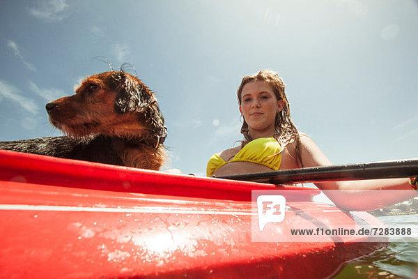 Teenagermädchen und Haushund im Kajak