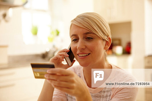 Woman using smartphone  holding credit card
