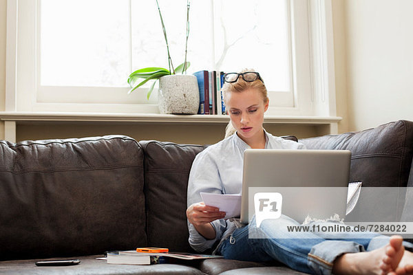 Junge Frau auf Sofa sitzend mit Laptop und Papieren