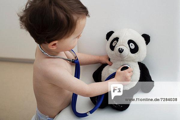 Kleiner Junge mit Stethoskop auf Pandaspielzeug