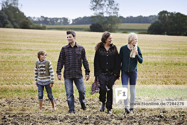 Family walking together in grassy field