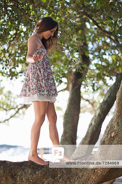 Woman balancing on a tree branch