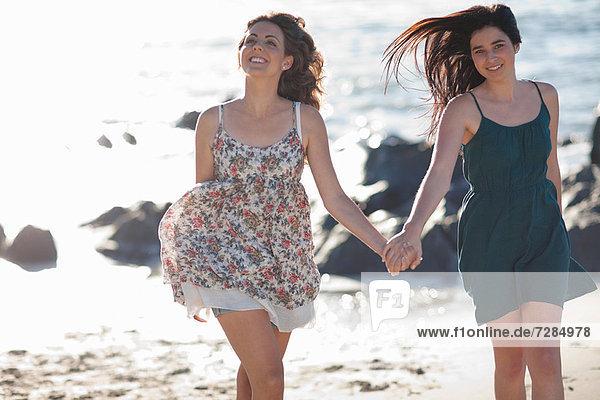 Frauen beim gemeinsamen Laufen am Strand