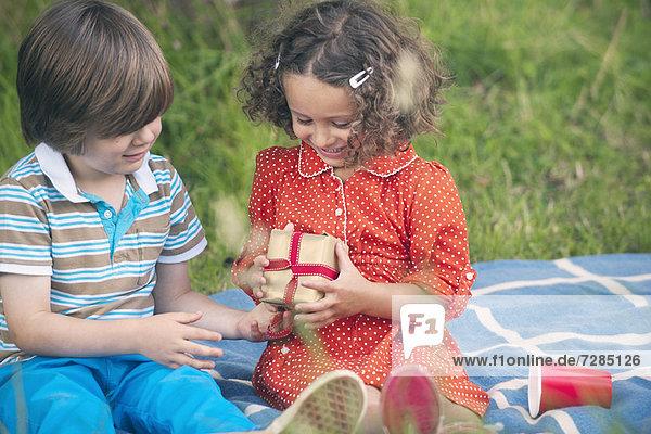 Junge schenkt beim Geburtstagspicknick