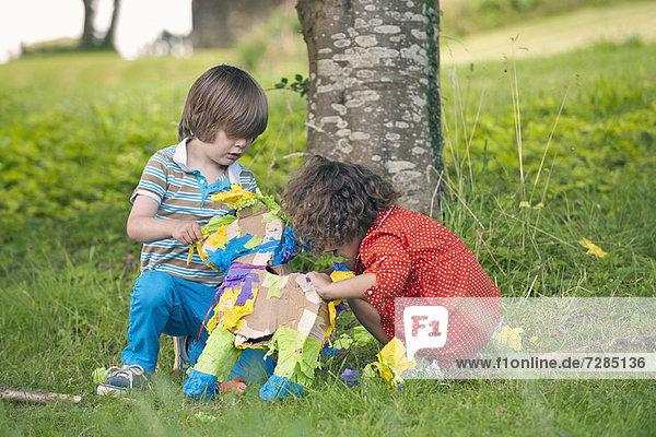 Kinder eröffnen pinata auf der Party