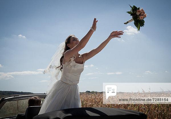 Neuvermählte Braut wirft Blumenstrauß aus dem Auto