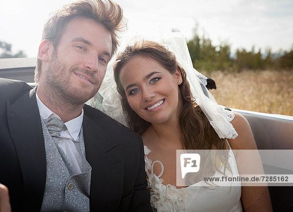 Neuvermähltes Paar im Cabriolet sitzend