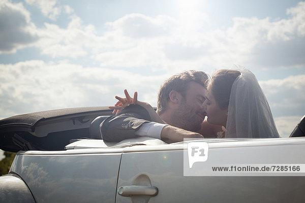 Neuvermähltes Paar im Begriff  sich in einem Cabrio zu küssen.