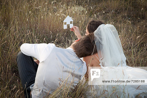 Neuvermähltes Ehepaar mit einem Hausbild