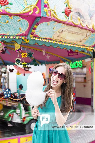 Frau isst Zuckerwatte auf der Messe