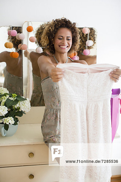 Lächelnde Frau bewundert neues Kleid