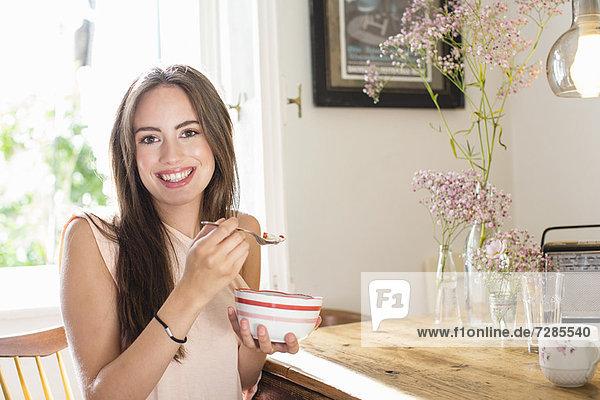 Lächelnde Frau beim Frühstücken