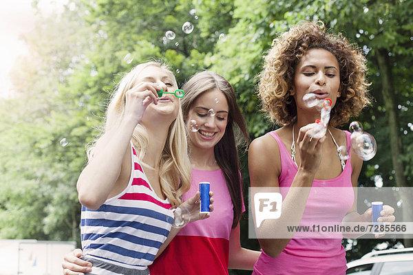 Lächelnde Frauen blasen Blasen im Freien.