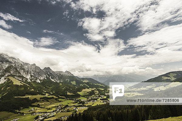 Wolken über grasbewachsener Landschaft