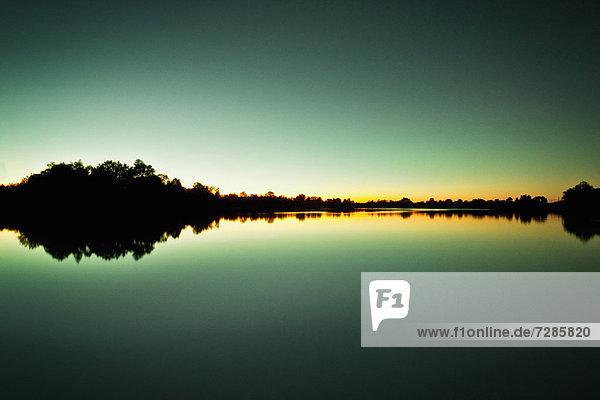 Himmel und Bäume spiegeln sich im stillen See wider