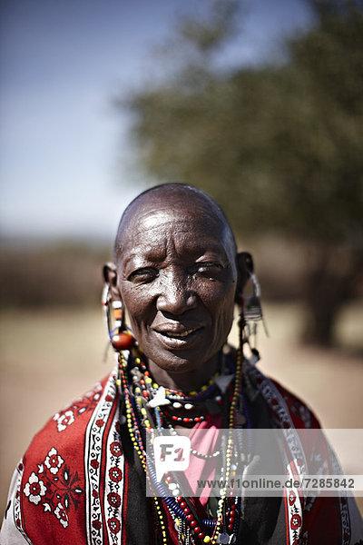 Lächelnde Maasai-Frau trägt Schmuck
