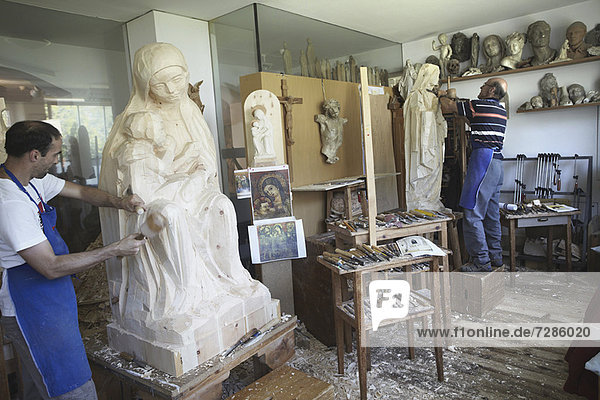 Bildhauer meißeln Figuren aus Holz