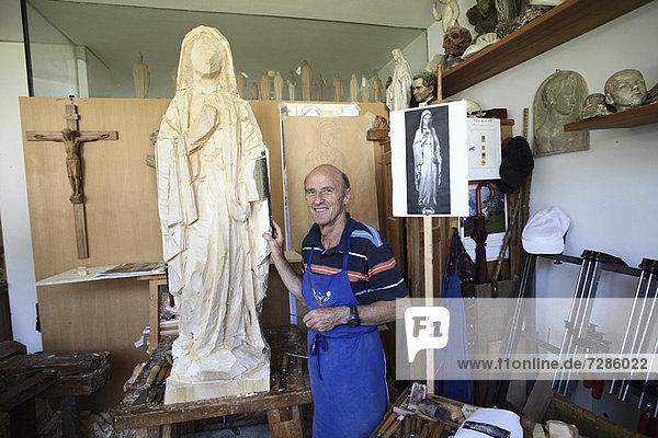 Bildhauer stehend mit Holzfigur