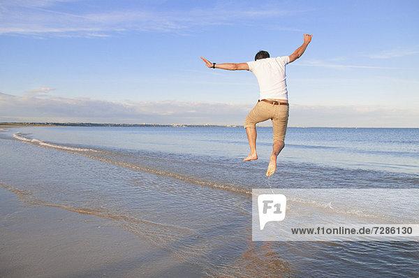 Mann springt vor Freude in den Wellen am Strand