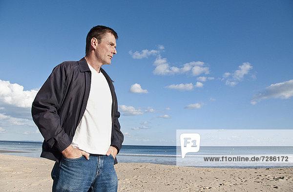 Ein ernsthafter Mann  der am Strand spazieren geht.