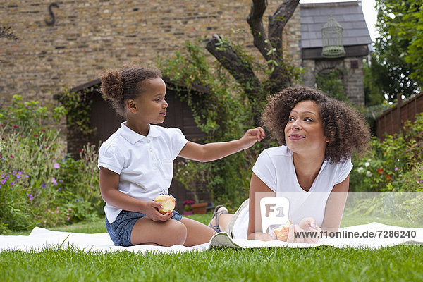 Mutter und Tochter beim Essen im Garten