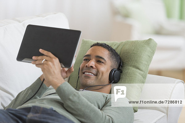 Mann  zuhören  Couch  Musik  Tablet PC