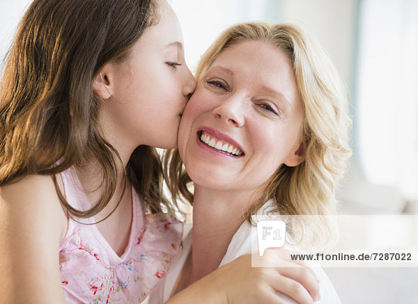 daughter (8-9 years) kissing mother