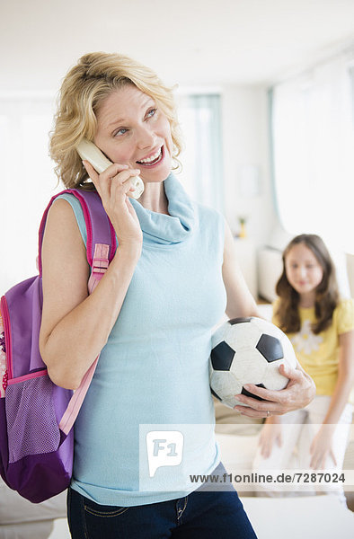 Mother talking on telephone and holding soccer ball  daughter in background