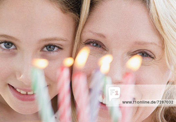 Portrait of mother and daughter (8-9 years) with birthday candles