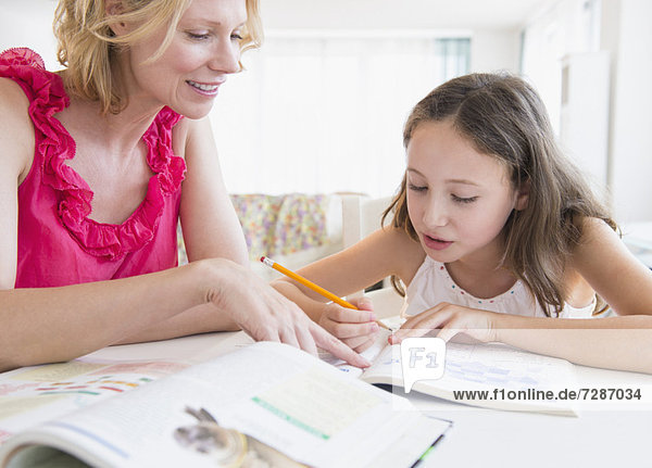 Mother and daughter (8-9 years) doing homework