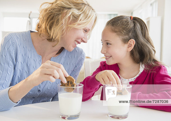 Mother and daughter (8-9 years) eating cookies with milk